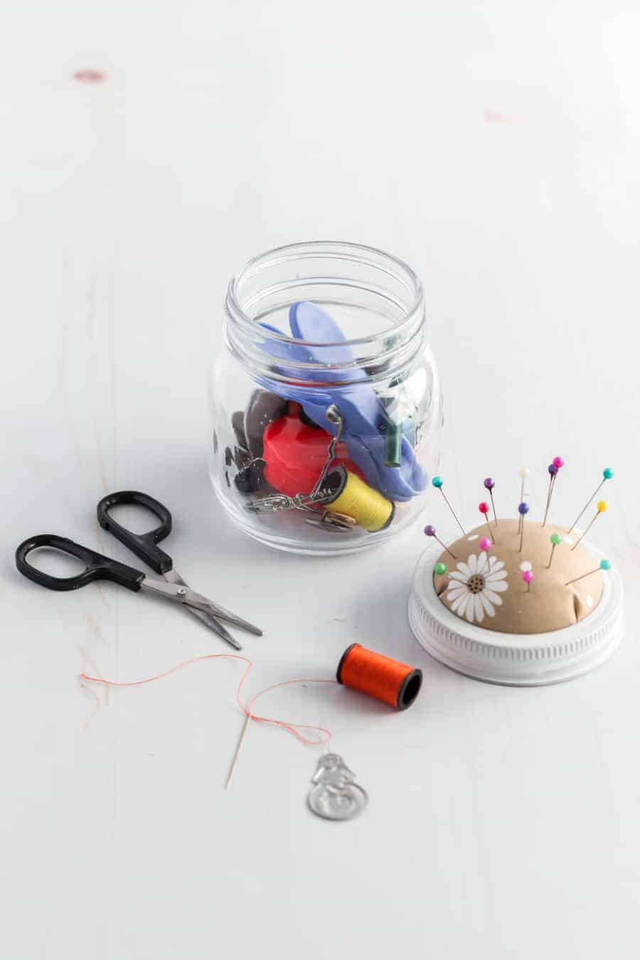 A jar full of sewing tools with scissors out by it, a threaded needle connected to the spool, a threader, and the jar lid made into a pin cushion.