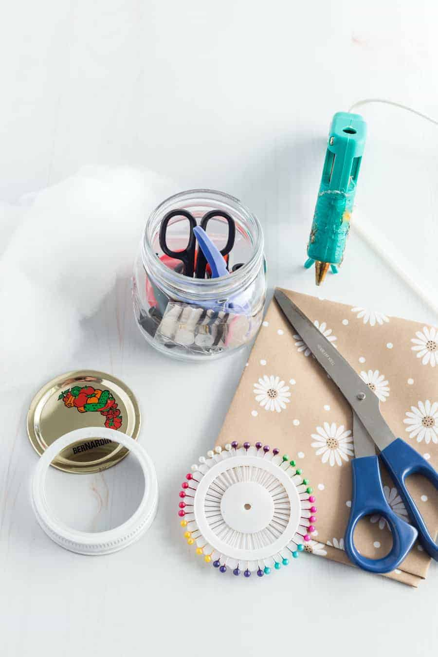 A clear jar with some sewing tools in it and the lid laid out. Some paper with scissors on it and glue gun nearby, as well as some pins.