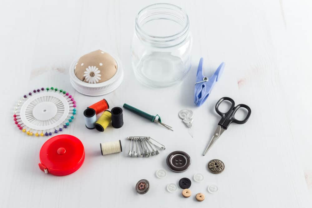 A small clear jar with sewing stuff around it, including, scissors, seam ripper, buttons, different color thread, a tape measure, and pins.