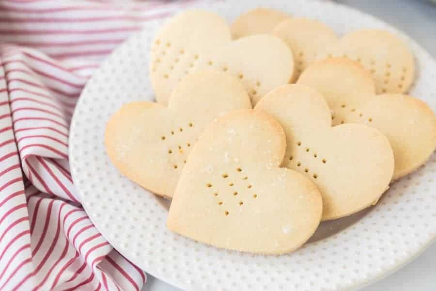 A white plate with heart shaped shortbread cookies on top of a red and white striped towel.
