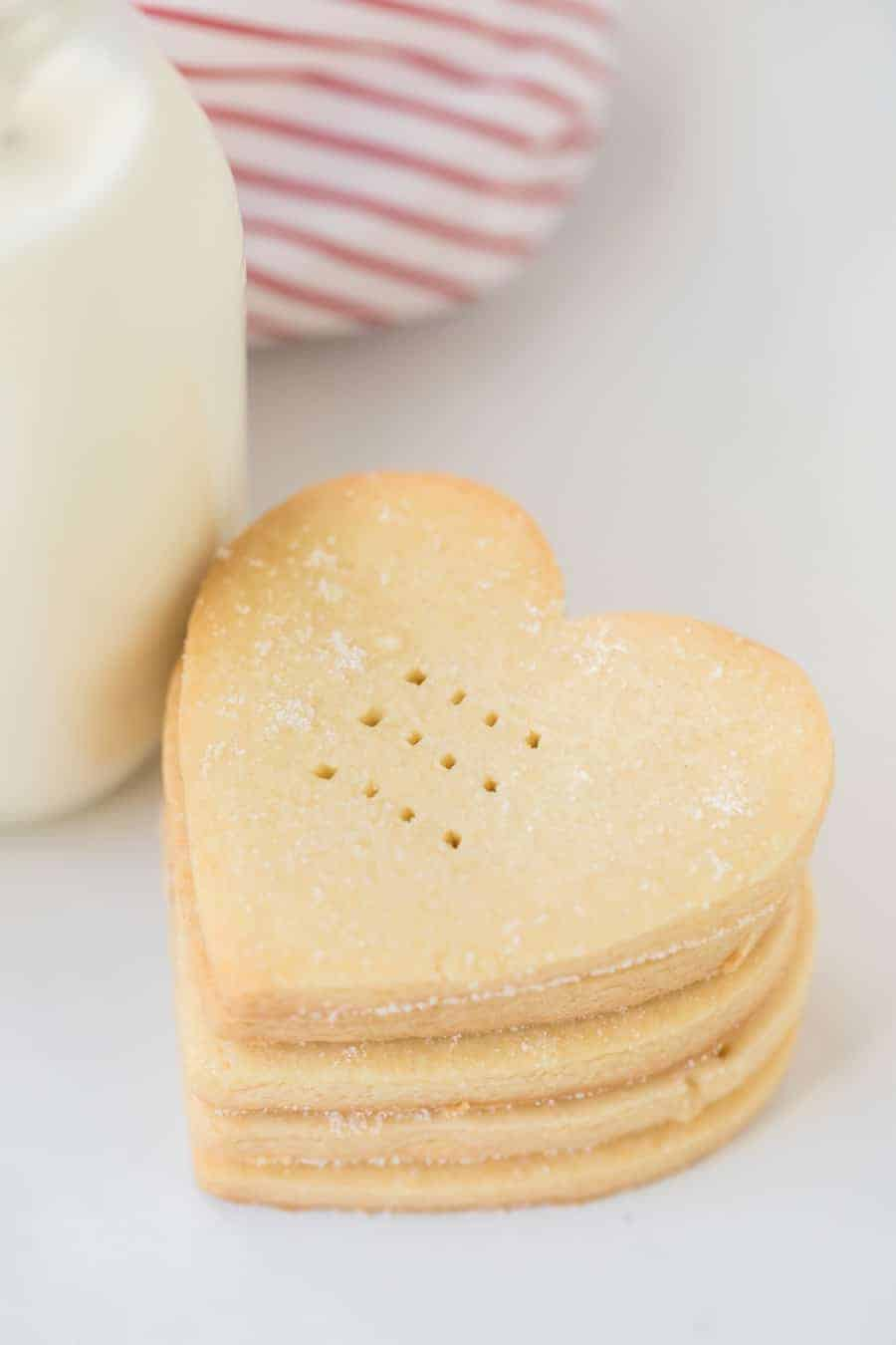 A close up of heart shaped shortbread cookies by a glass jug of milk.