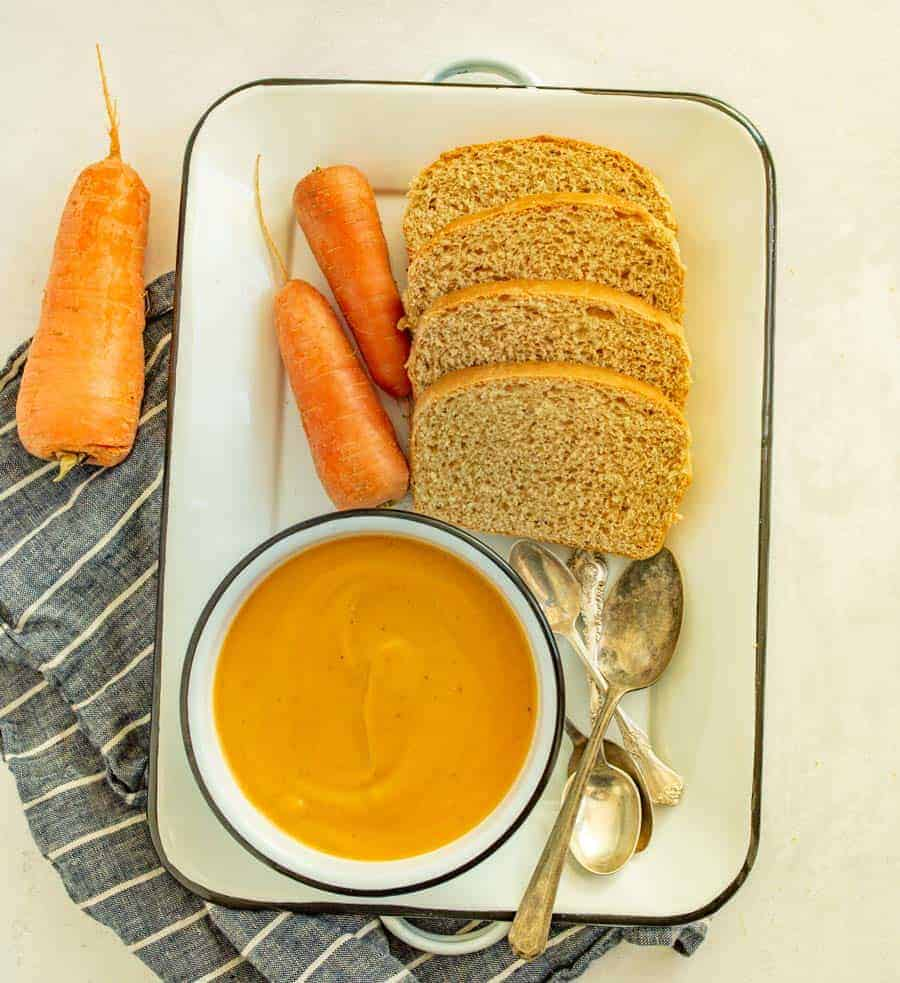 tray with bowl of carrot soup and homemade bread