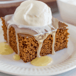 A square piece of gingerbread cake on a white plate topped with vanilla caramel sauce and whipped cream