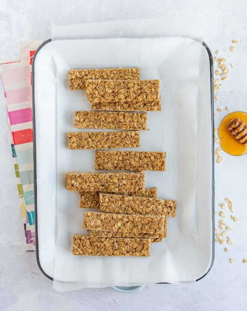 Homemade granola bars in a parchment-lined white rectangular pan