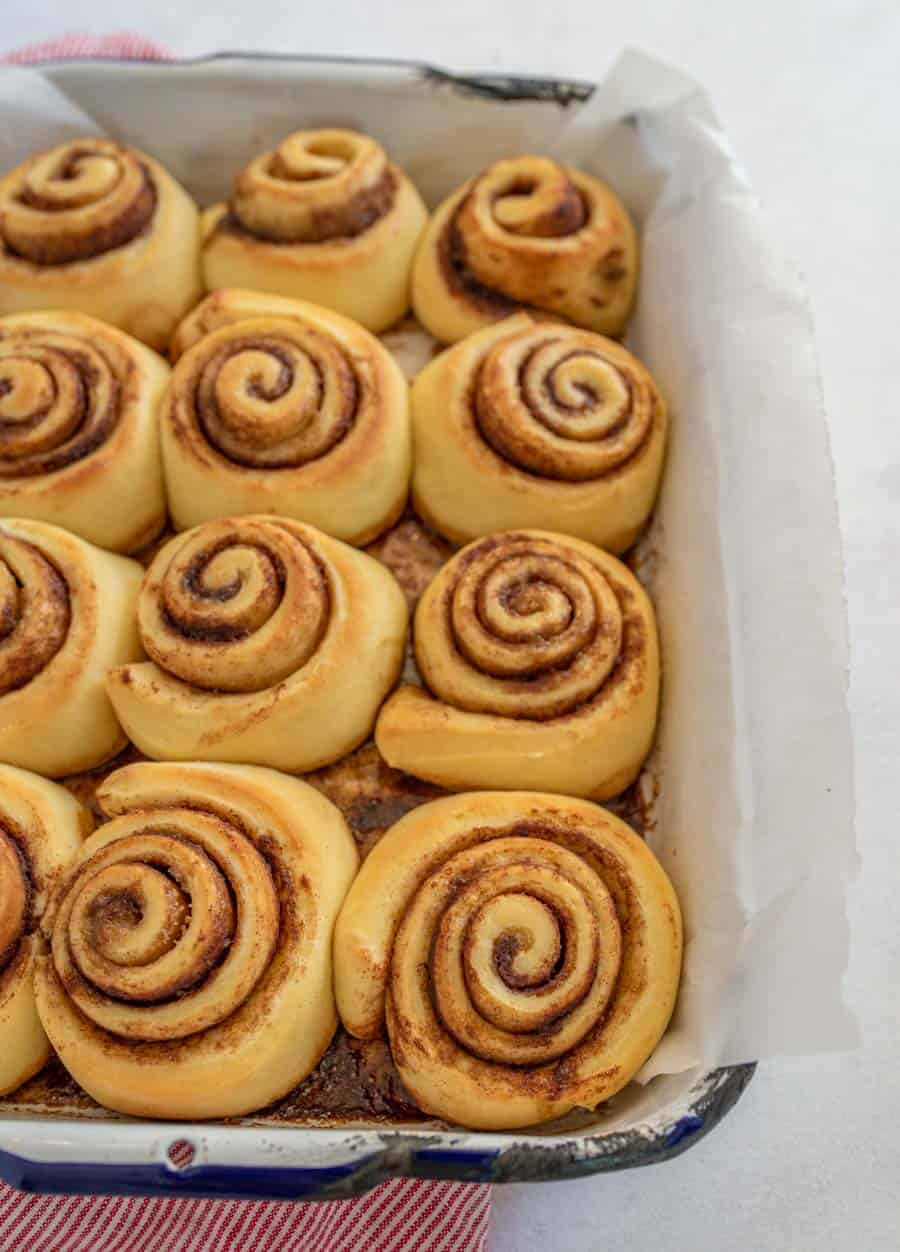 An overhead view of almost a full pan of cooked cinnamon rolls.