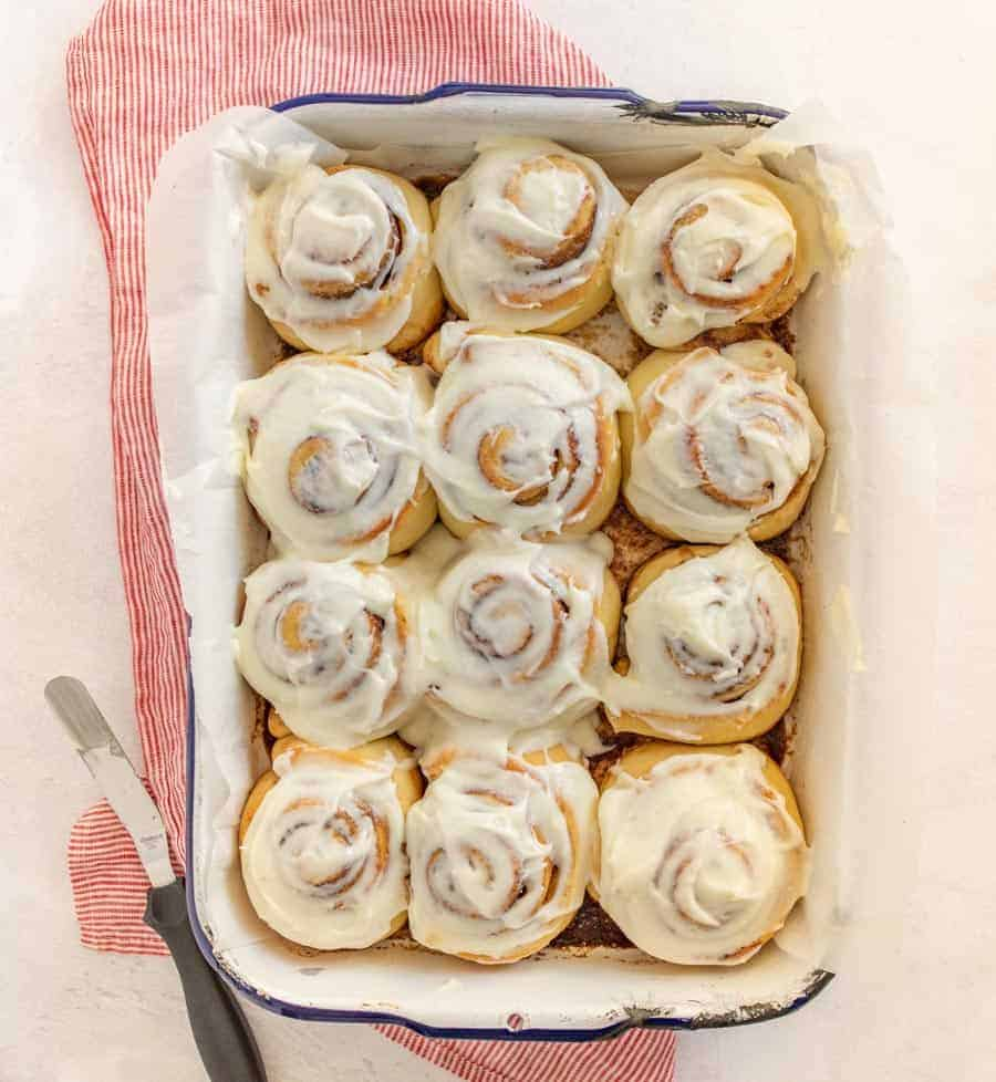 An overhead shot of the finished cinnamon rolls in a pan on top of a red and white striped towel. The bottom left-hand corner has the utensil used to frost the cinnamon rolls.