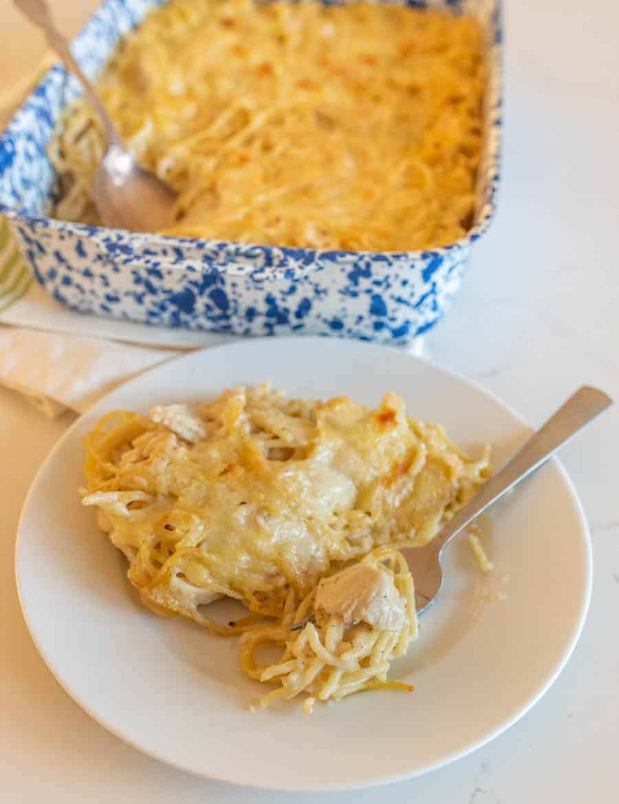 A small white plate with a serving of the turkey tetrazzini on it, including a silver fork. In the background is the dish the serving has been taken from, including a silver serving spoon.