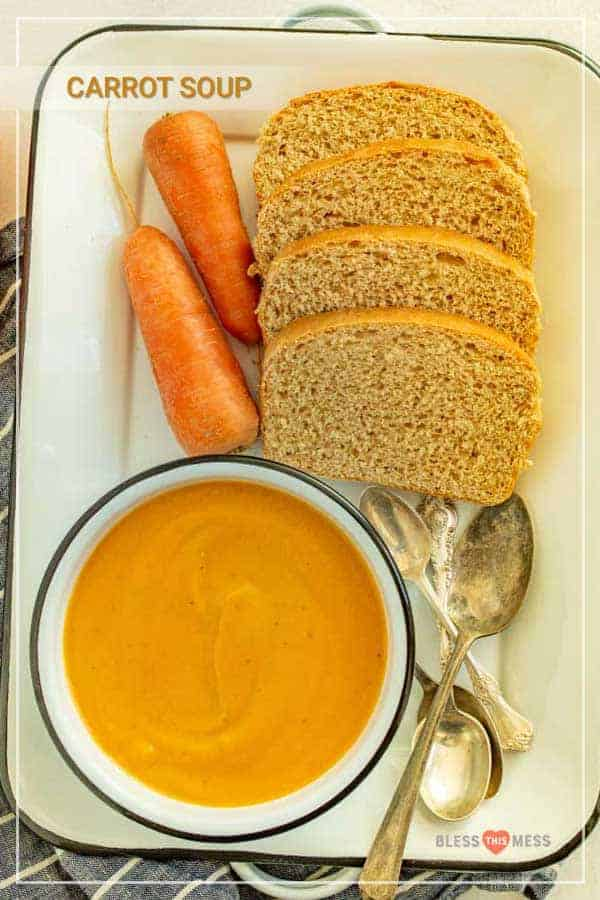 carrot soup in a bowl with spoons ready to serve and a side of wheat bread