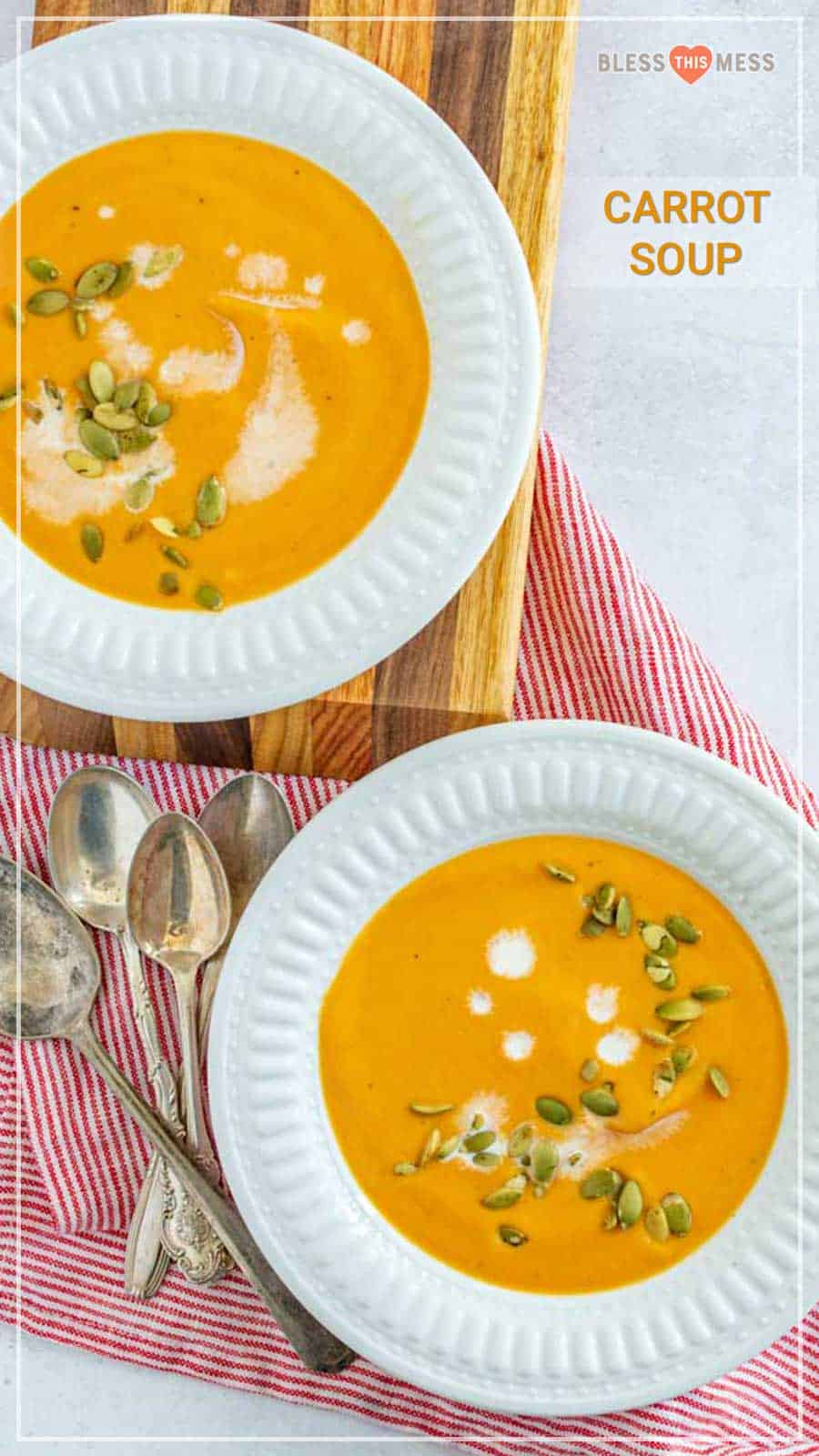 two bowls of carrot soup garnished with cream and pumpkin seeds