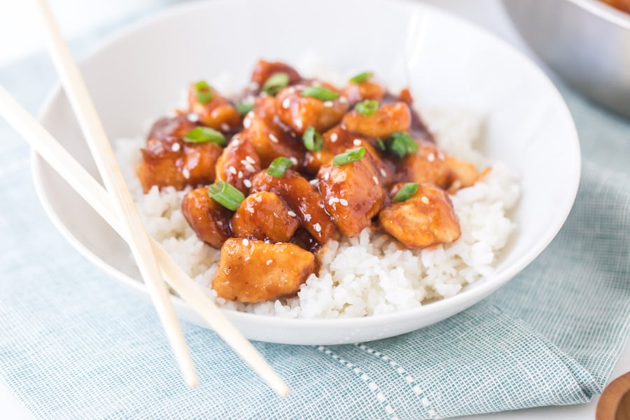 general tso's chicken with white rice in white bowl with chopsticks