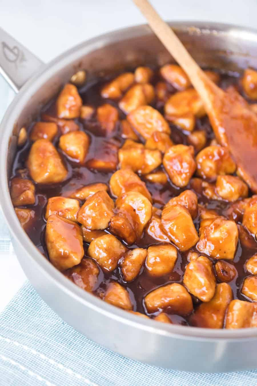 general tso's chicken in skillet with wooden spoon
