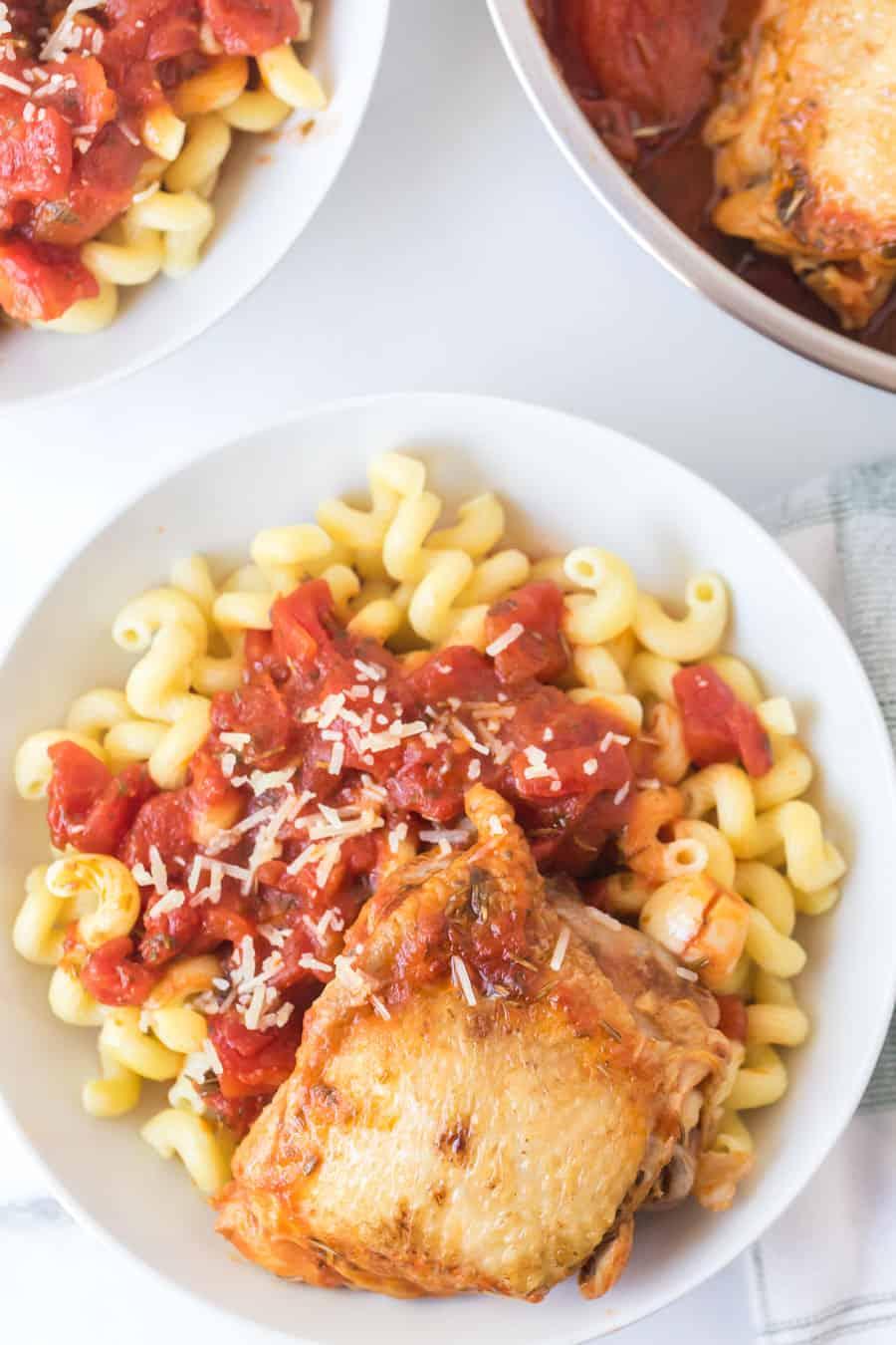 tomato and garlic cavatappi pasta with chicken thigh in white bowl