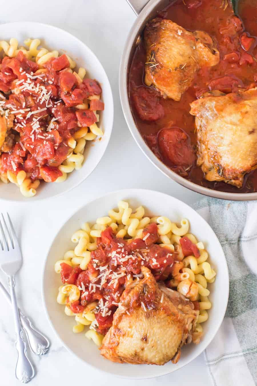 tomato and garlic cavatappi pasta with chicken thigh in white bowls and chicken thighs with garlic tomato sauce in skillet