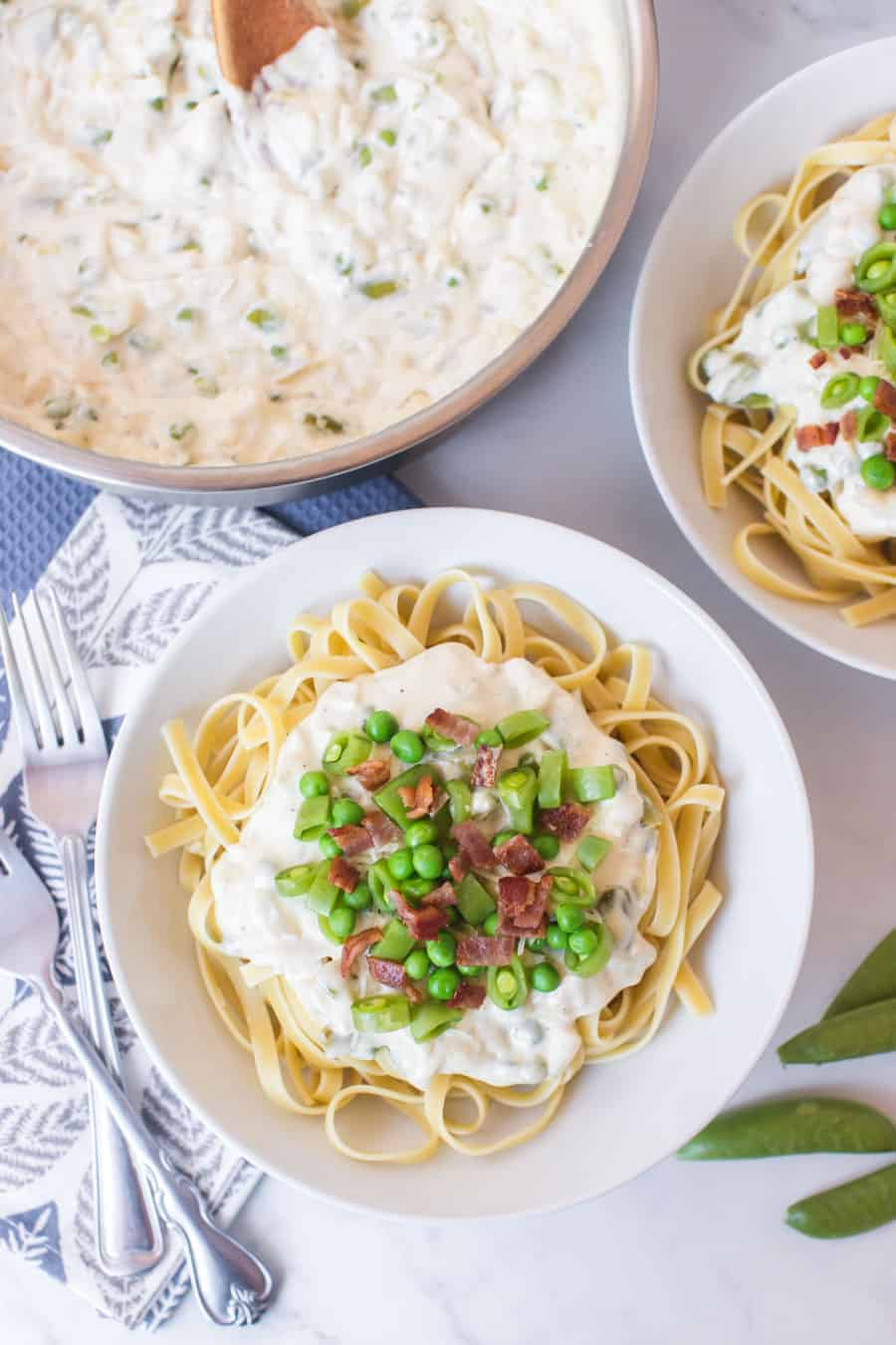 two round white bowls of creamy bacon and peas pasta next to pot of