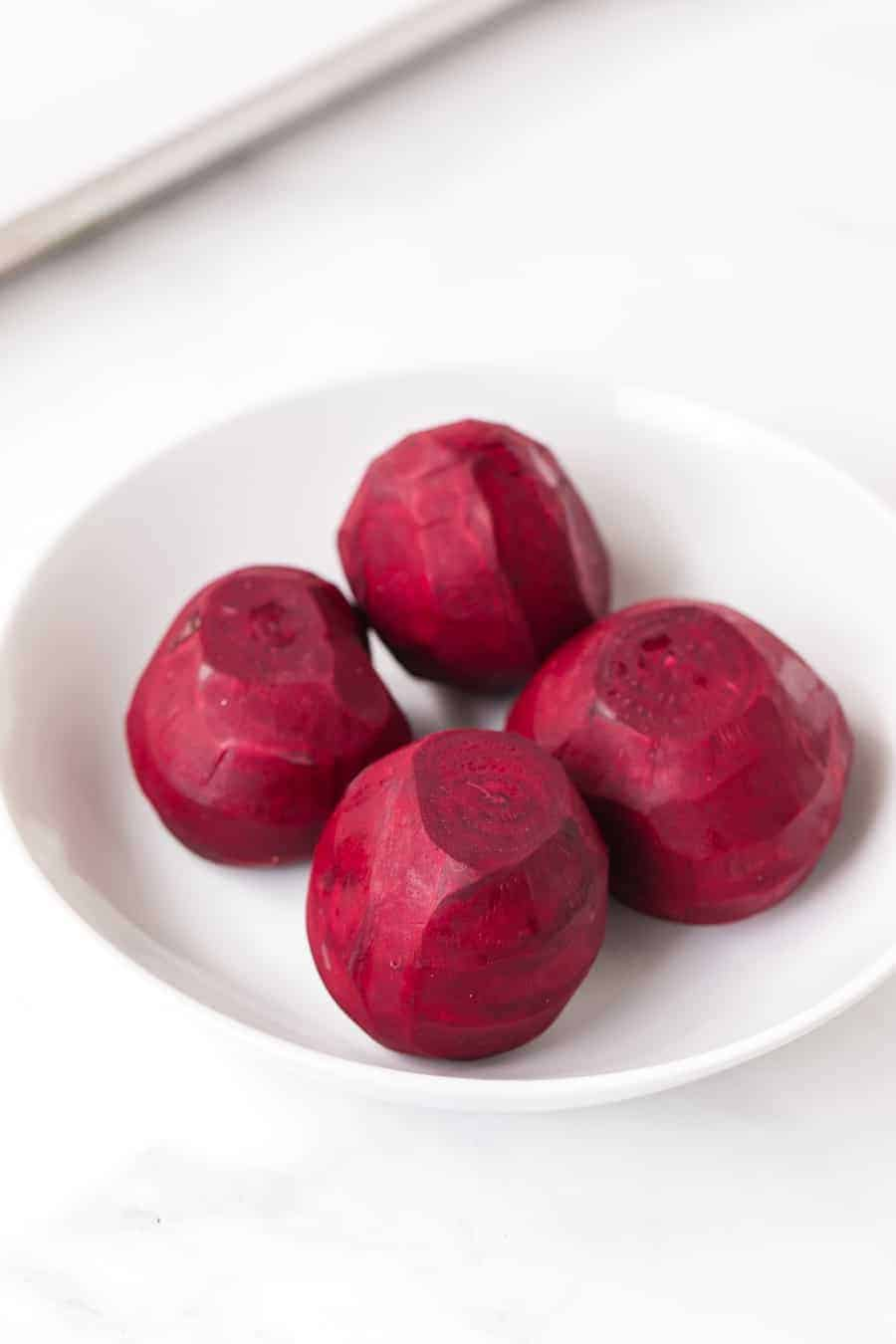 skinned uncooked beets in round white bowl