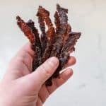 woman holding beef jerky strips closeup