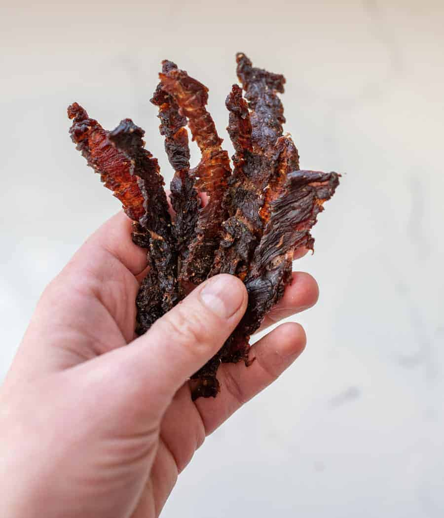 woman holding strips of beef jerky