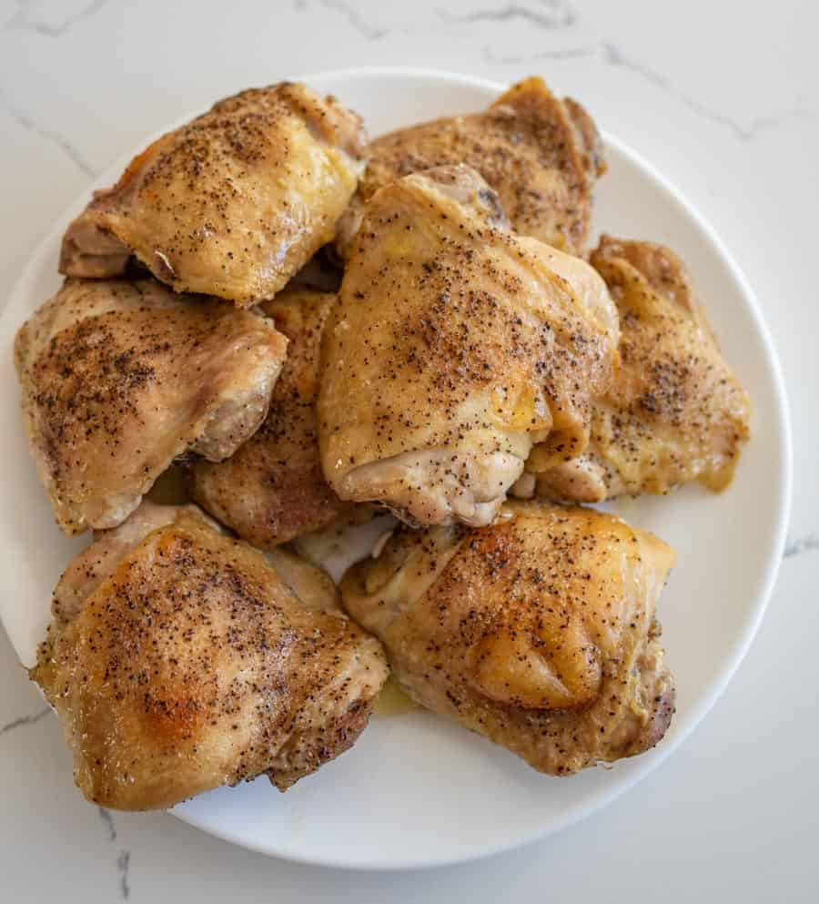 baked chicken thighs on round white plate on white countertop