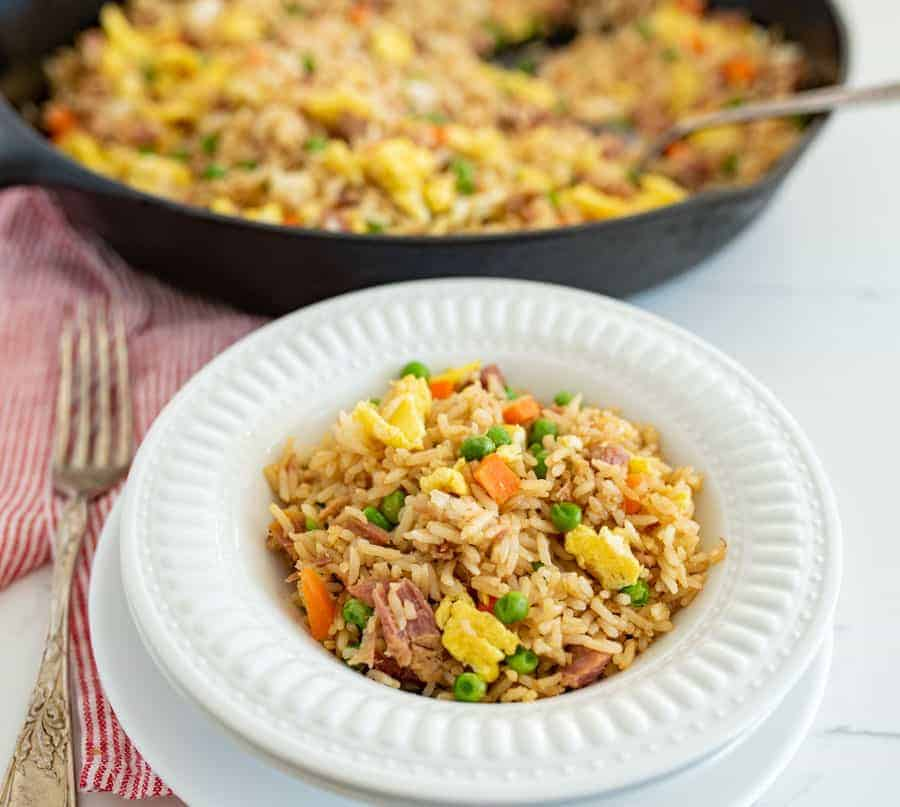 white bowl of fried rice with ham next to fork and skillet of easy fried rice
