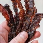woman holding beef jerky strips