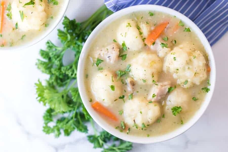 small white round bowl of chicken and dumplings soup