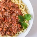 round white bowl of homemade bolognese sauce with garnish on white tablecloth