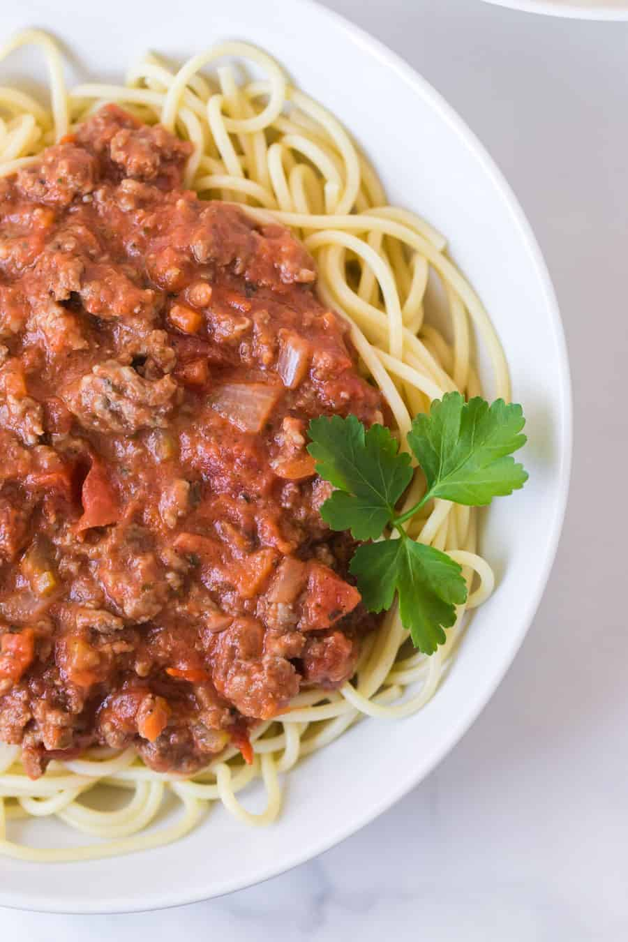 round white bowl of spaghetti with homemade bolognese sauce and garnish