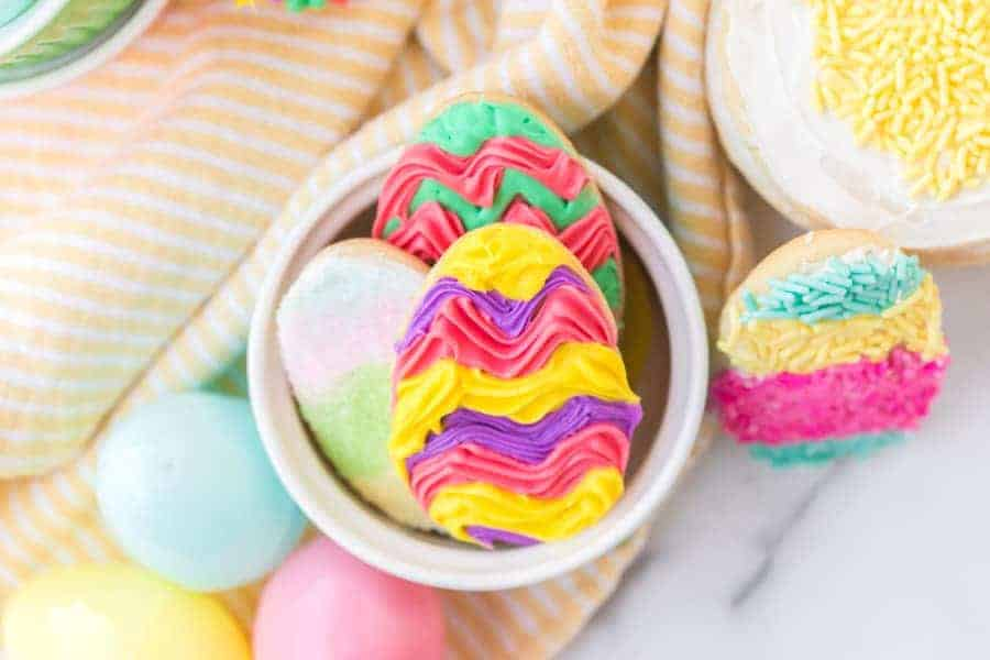 frosted easter sugar cookies in white ramekin and plastic easter eggs on yellow and white striped towel