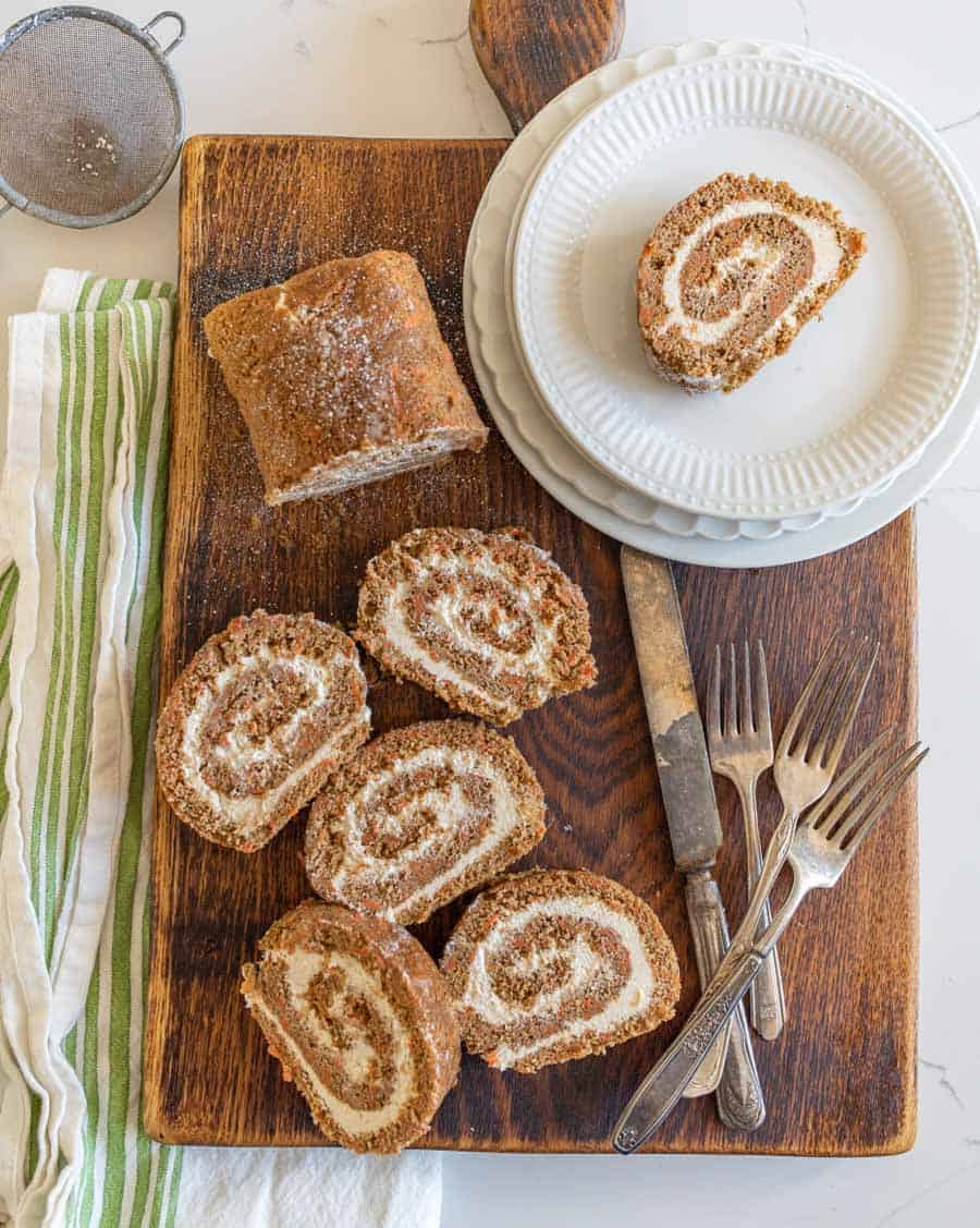 overhead shot of carrot cake roll slices on cutting board with utensils and round dessert plates