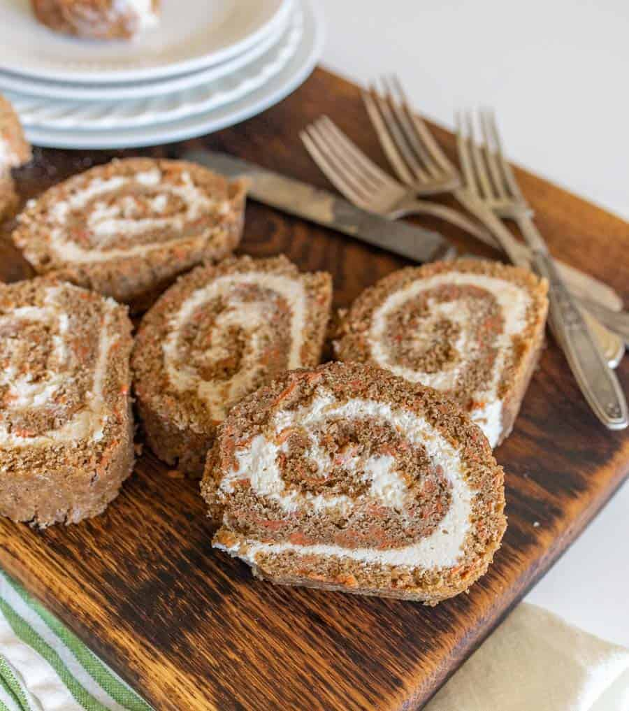 slices of carrot cake roll on wooden cutting board with forks and round white dessert plates
