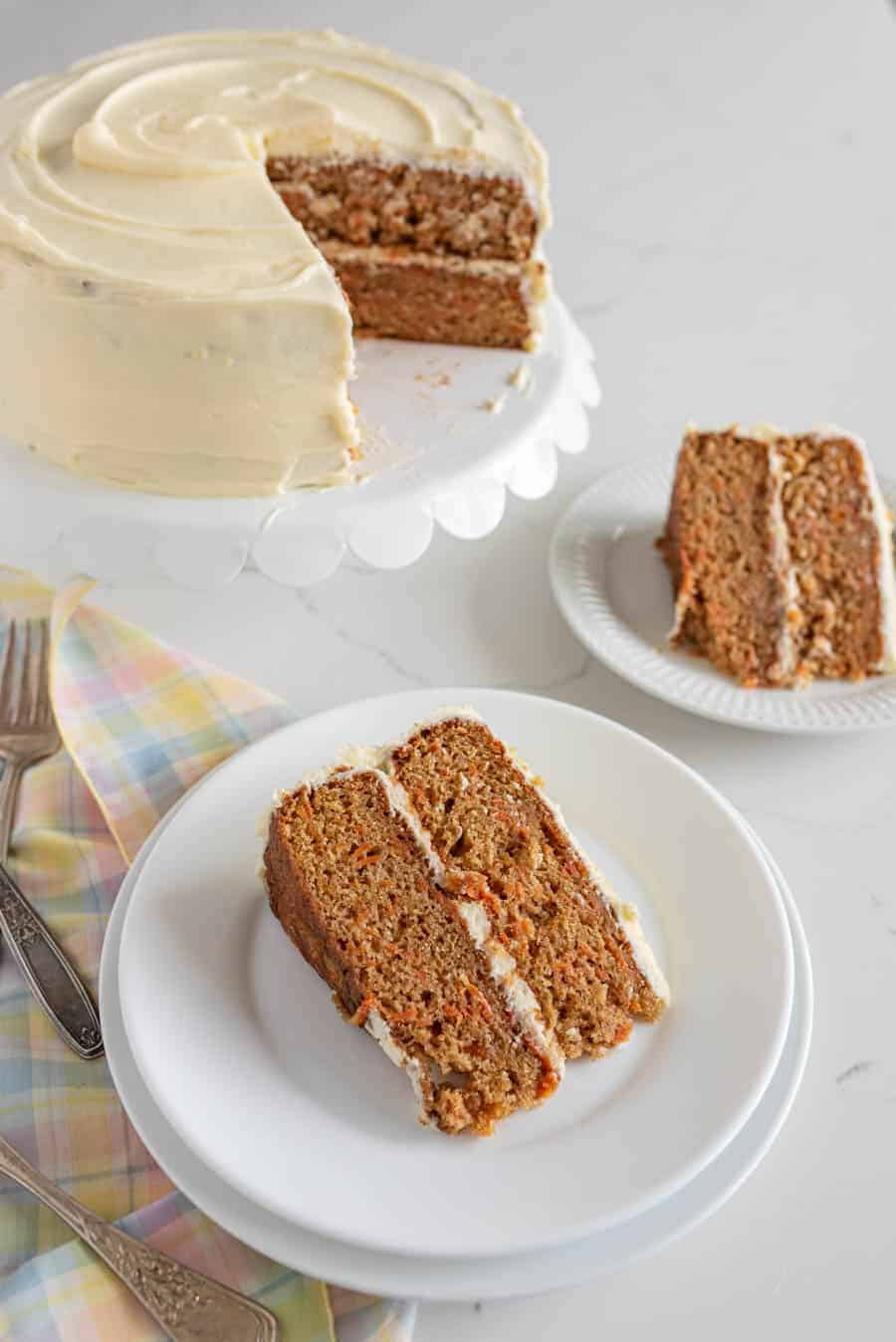 carrot cake on white cake stand next to slices of carrot cake on two round white plates with plaid pastel napkin