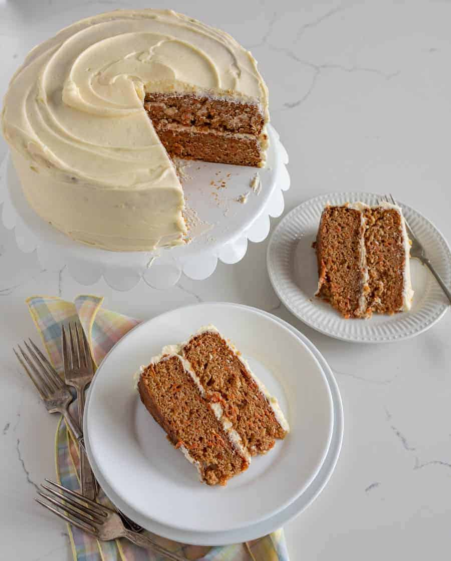 carrot cake with slice missing sitting on white cake stand with two slices of cake on round white plates on white surface with forks