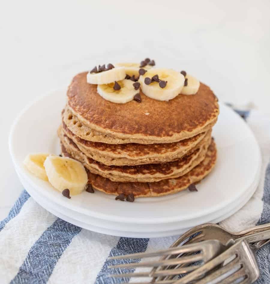 stack of banana pancakes with banana slices and chocolate chips on stack of white plates with forks