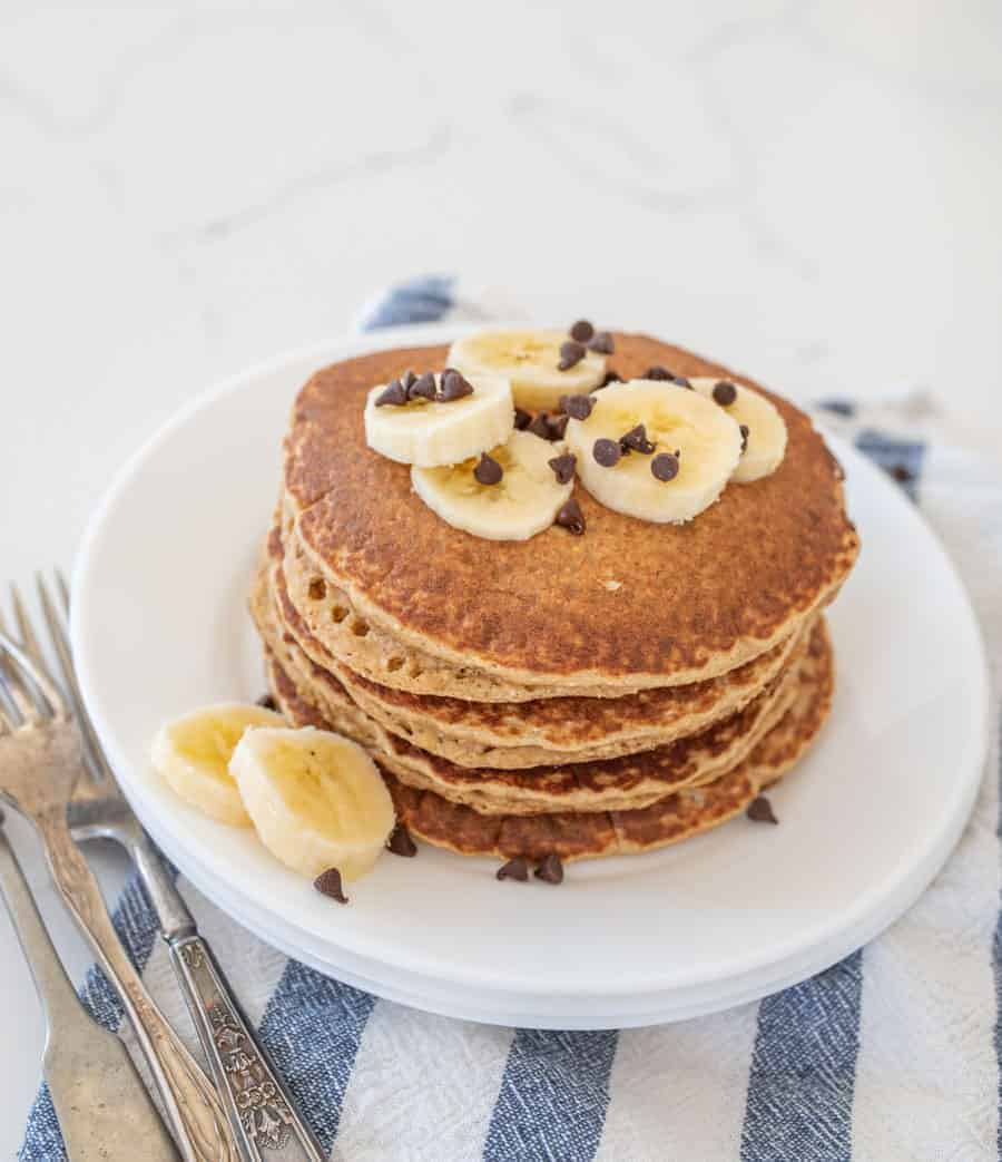 stack of banana pancakes on round white plates with forks and blue and white striped towel