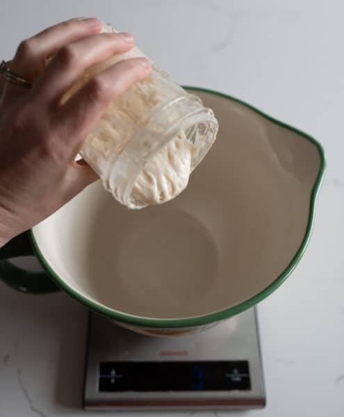 woman pouring sourdough starter in measuring cup
