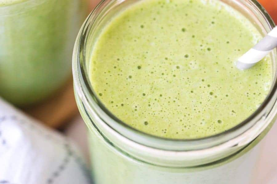 closeup of healthy green smoothie with gray and white paper straw