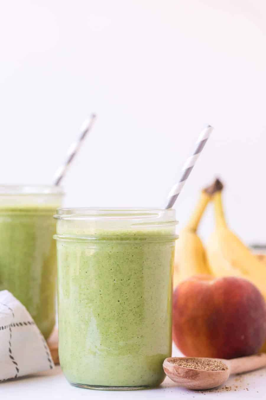 two healthy green smoothies in glass jars with paper straws next to an apple and bananas