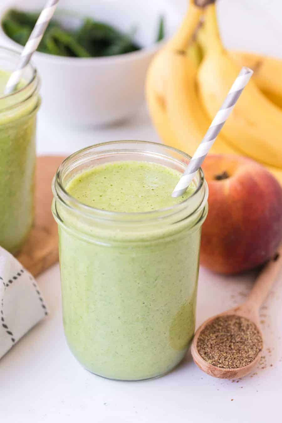 healthy green smoothie is clear jar with a gray and white paper straw next to spinah apple cinnamon and bananas