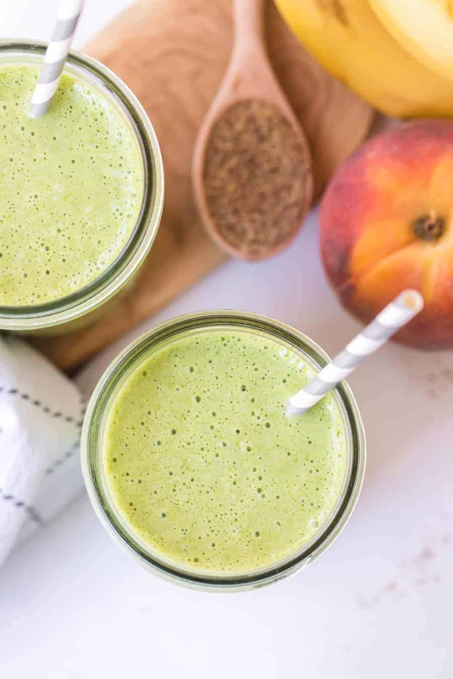 overhead shot of healthy green smoothies with gray and white paper straws on white countertop with peaches and bananas