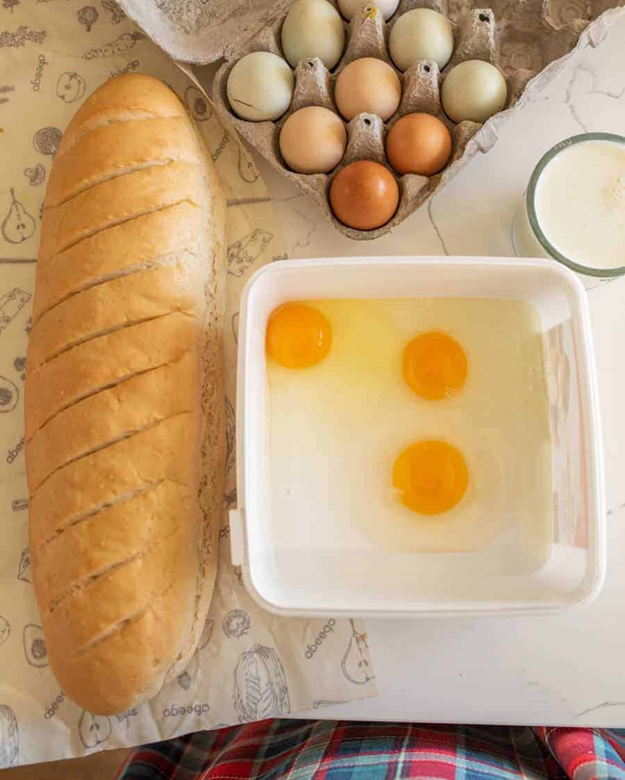 loaf of bread on counter next to bowl of eggs and carton of eggs