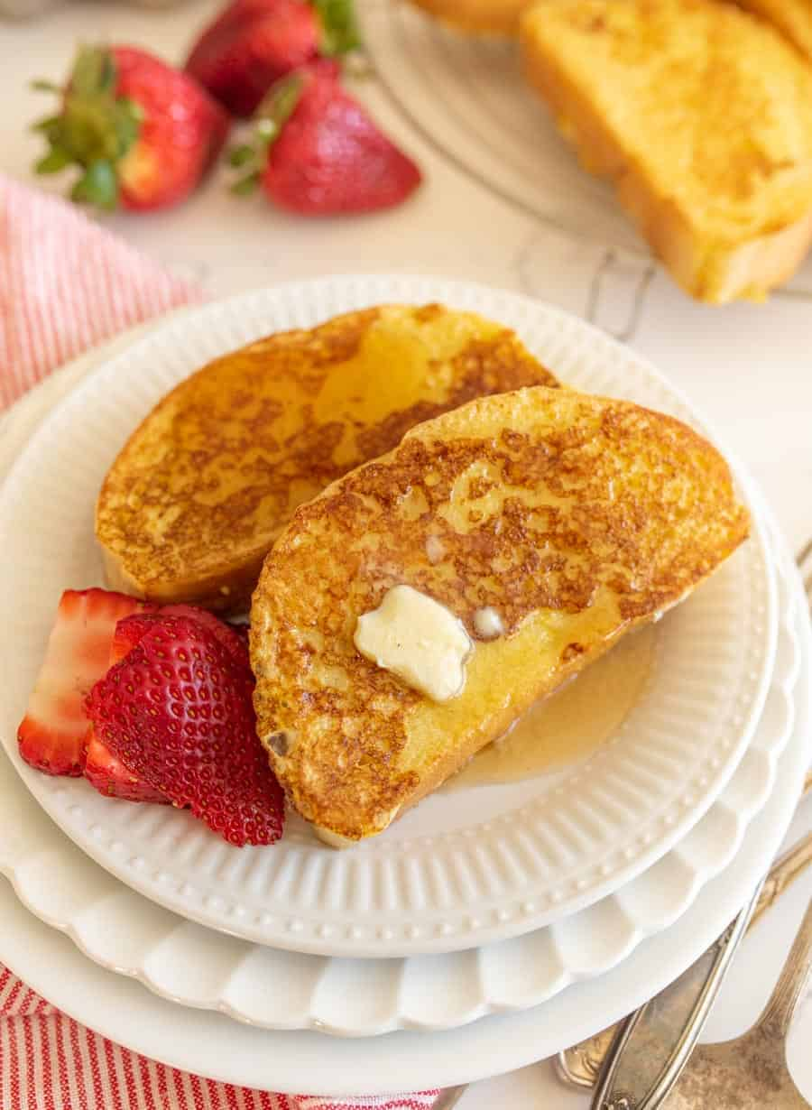 closeup image of two slices of french toast with butter and strawberries on round white plates