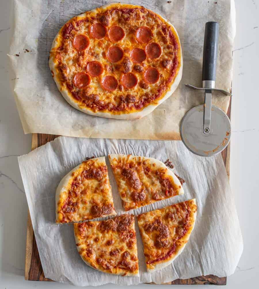 pepperoni sourdough pizza and cheese sourdough pizza on parchment with pizza cutter