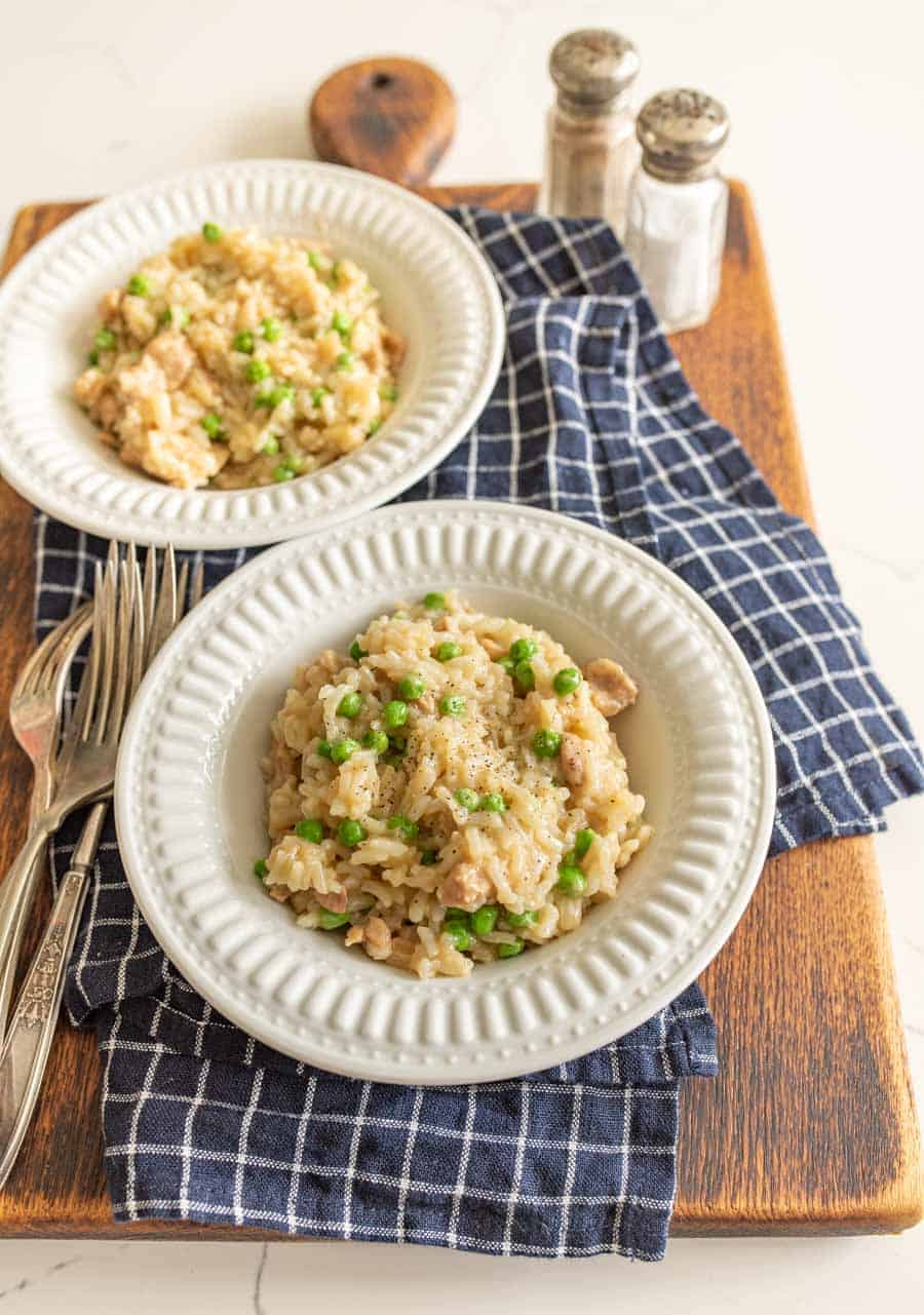instant pot chicken and rice in white bowls on blue and white towel on cutting board with silverware