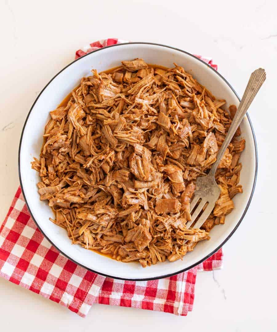 pulled pork on white serving platter with red check cloth