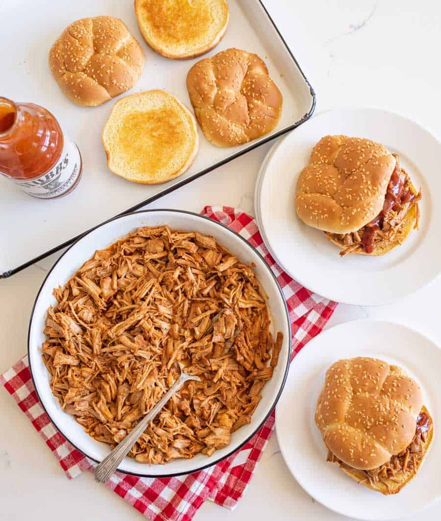 table setting of pulled pork, sandwiches on plates, toasted bun on pan
