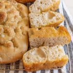 baked sourdough focaccia bread baked and sliced on cooling rack