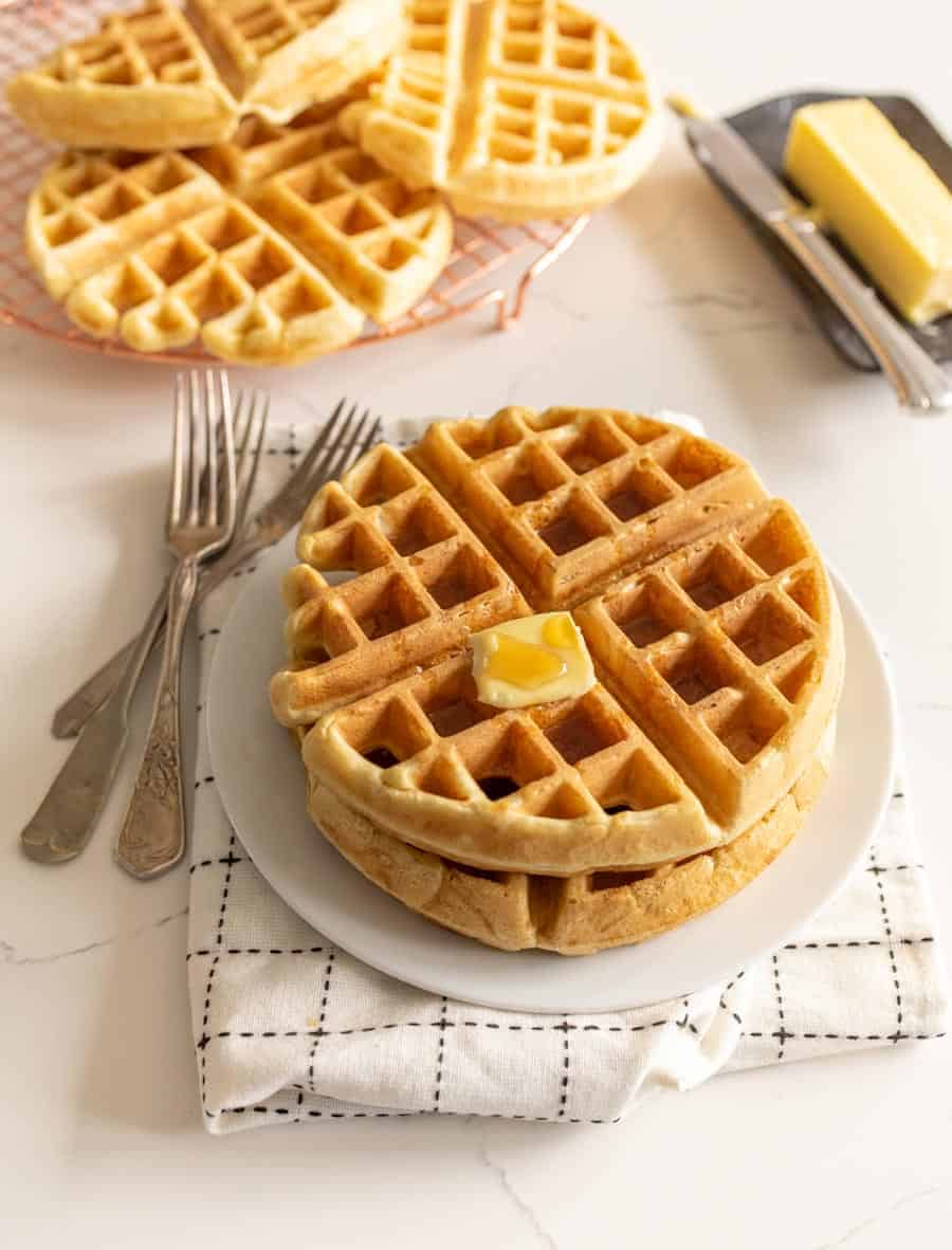 two sourdough waffles with butter on white plates with forks next to stick of butter and waffles on cooling rack