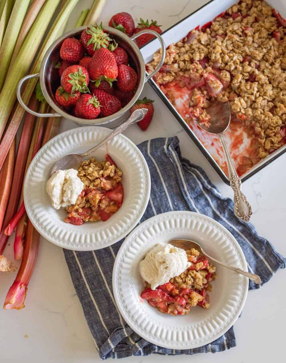 two bowls of dished crisp with ice cream on top next to pan of baked strawberry rhubarb crisp