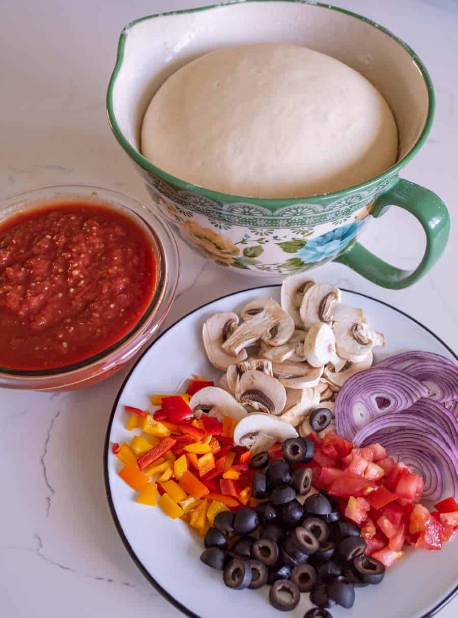 plate of olives tomato red onion bell pepper and mushrooms with pizza sauce and dough rising