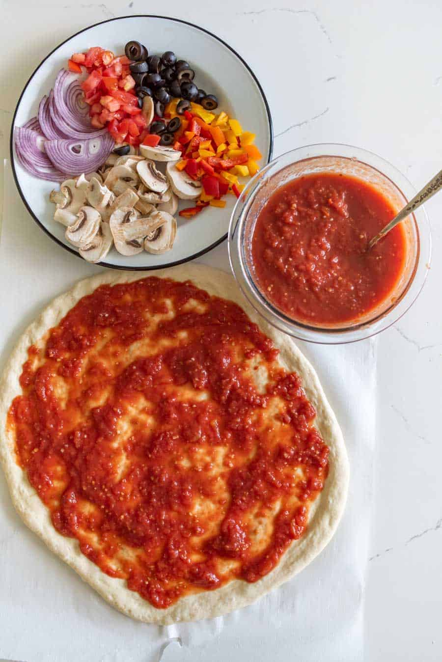 overhead shot of pizza dough with pizza sauce and bowl of pizza toppings